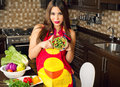 Beautiful woman serving home made salad in her kitchen Royalty Free Stock Photos