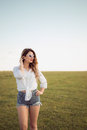 Beautiful woman with sexy legs and denim shorts  on grass, shoe less Royalty Free Stock Photo
