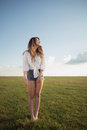 Beautiful woman with sexy legs and denim shorts jumping  on grass, shoe less Royalty Free Stock Photo