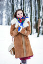 Beautiful woman in sheepskin coat in winter forest Stock Photo
