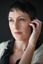 Beautiful woman with short brown hair talking on a cell phone older and eyes Royalty Free Stock Images