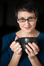 Beautiful woman with short hair and coffee cup on black backgrou older brown eyes glasses a background Royalty Free Stock Photo