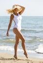 Beautiful woman, simple white swimsui, sun hat at beach Royalty Free Stock Photo