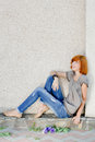 Beautiful woman sitting against wall looking up Stock Photography