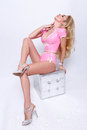 Beautiful woman sitting astride on pufie with long legs in a pink costume barbie and gran barbie Royalty Free Stock Photo