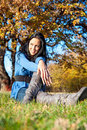 Beautiful woman sitting in the autumn park Stock Photos