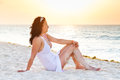Beautiful woman sitting beach sunrise Stock Image