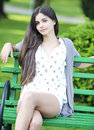 Beautiful woman sitting on bench outdoor teen in the park a summer day Stock Photos