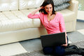 Beautiful woman sitting on the floor with laptop middle aged at home Stock Photos