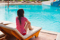 Beautiful woman sitting on a lounger pool background the Royalty Free Stock Photography