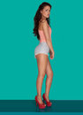 Beautiful woman in skimpy shorts with long wavy brunette hair standing sideways and high heels on a turquoise background Stock Photos