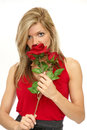Beautiful woman smelling a rose with red flowers Royalty Free Stock Photos