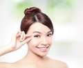 Beautiful woman smile face and finger touch her eyes with clean skin concept for eye skin care over nature green Stock Photos