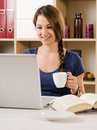 Beautiful woman smiling while using a laptop photo of and drinking coffee at home or at her office Stock Photos