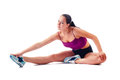 Beautiful woman in sportswear does exercises sitting on floor Royalty Free Stock Photography