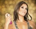 Beautiful woman spraying perfume tanned on herself Stock Photo