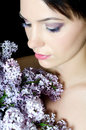 Beautiful woman with spring flowers of a lilac Royalty Free Stock Photography
