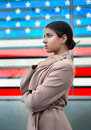 Beautiful woman standing in front of american flag and looking to the side. People nation patriotism concept Royalty Free Stock Photo