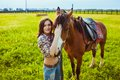Beautiful woman standing near a horse young Stock Images