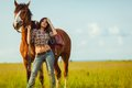 Beautiful woman standing near a horse young Stock Image