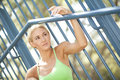 Beautiful woman staring blonde off in the distance with her arm up on a railing Stock Images