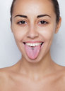 Beautiful woman sticking out her tongue and showing young piercing Royalty Free Stock Photo