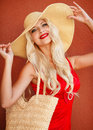 Beautiful woman in straw hat with large brim blonde long thick curly hair and gray green eyes makeup and red lipstick a yellow Stock Photo