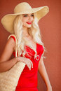 Beautiful woman in straw hat with large brim blonde long thick curly hair and gray green eyes makeup and red lipstick a yellow Stock Image