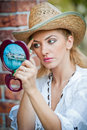 Beautiful woman with straw hat and mirror young looking in cosmetic good looking doing make up in Royalty Free Stock Image