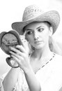 Beautiful woman with straw hat and mirror young looking in cosmetic good looking doing make up in Royalty Free Stock Photos