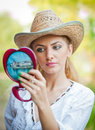 Beautiful woman with straw hat and mirror young looking in cosmetic good looking doing make up in Stock Photography
