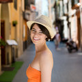 Beautiful woman on a street in palma de mallorca young trendy straw hat and colourful orange summer dress standing smiling at the Royalty Free Stock Image