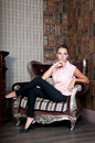 Beautiful woman in studio, luxury style. Beige blouse. In chair Royalty Free Stock Photo