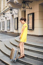 Beautiful woman with the suitcase at the entrance to the hotel Royalty Free Stock Photo