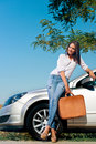 Beautiful woman with suitcase leaning on a car Stock Images