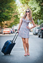 Beautiful woman with suitcases crossing the street in a big city sunglasses on and holding Stock Photos