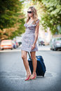 Beautiful woman with suitcases crossing the street in a big city sunglasses on and holding Royalty Free Stock Photos