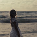 Beautiful woman in summer dress standing in ocean on sunset evei eveing background Stock Photography