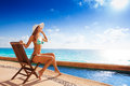 Beautiful woman sunbathes sitting on wooden chair young under bright sun while stoned pier near to the ocean in summer Royalty Free Stock Images