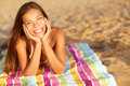 Beautiful woman sunbathing on the beach lying a towel facing camera with her chin cupped in her hands and a lovely Royalty Free Stock Images