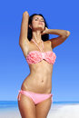 Beautiful woman sunbathing on beach in pink bathing suit Stock Image