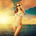 Beautiful woman sunbathing at the seaside holding fashion swimsuit and sun glasses Royalty Free Stock Photo