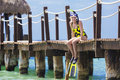Beautiful woman on a sunny beach vacation sitting pier in her snorkel and diving gear ready to go have fun her resort Royalty Free Stock Photos