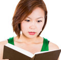 Beautiful woman surprised by the story she is reading in her book young Stock Image
