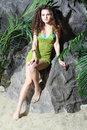 Beautiful woman in swimsuit and jersey sits on stone green near gray rocks Stock Photography