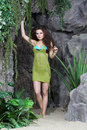 Beautiful woman in swimsuit and jersey stands next to rocks green gray with greenery Royalty Free Stock Image