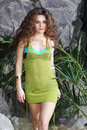 Beautiful woman in swimsuit and jersey walks green near gray rocks Royalty Free Stock Photography