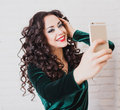 Beautiful woman take a self portrait with her smart phone pretty girl in green dress doing selfie Royalty Free Stock Photography