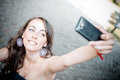 Beautiful woman taking self portrait with smart phone in the city Stock Image