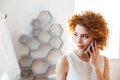 Beautiful woman talking on cell phone in office Royalty Free Stock Photo